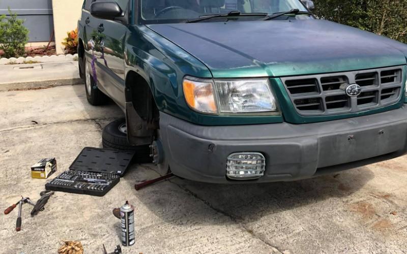 Photo of green Suburu getting front brakes replaced as well as wheel bearings in Orange, California.