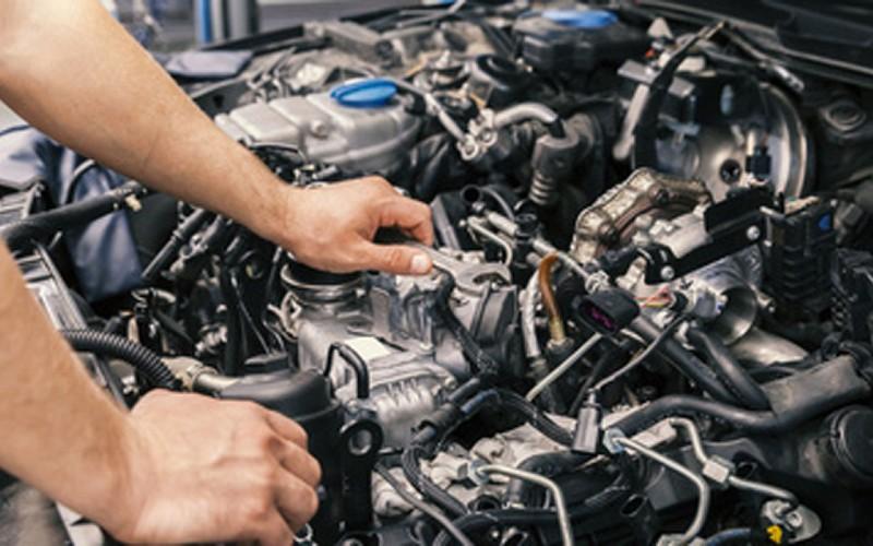 Photo of mechanic tuning an car's carburetor.